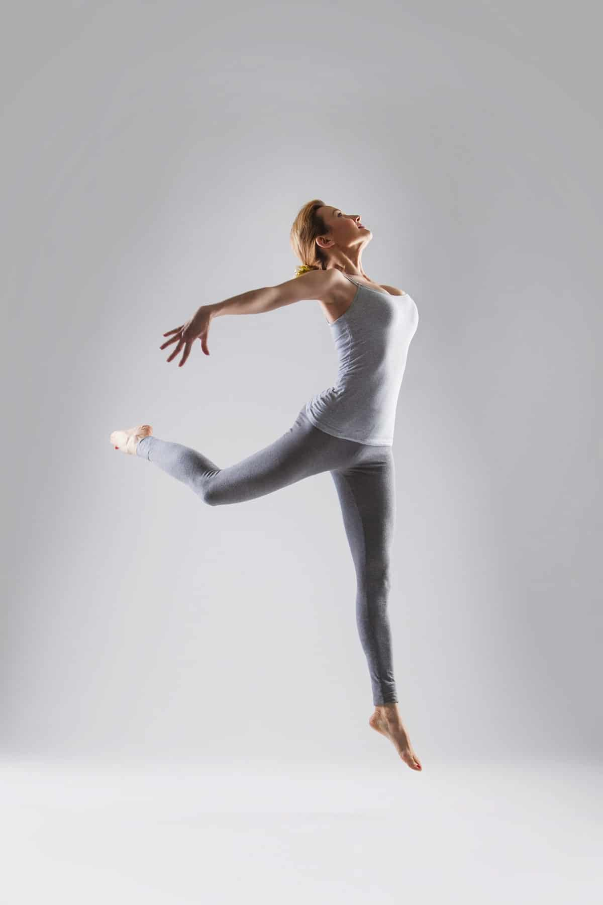 Sporty beautiful ballet dancer woman posing on a grey background
