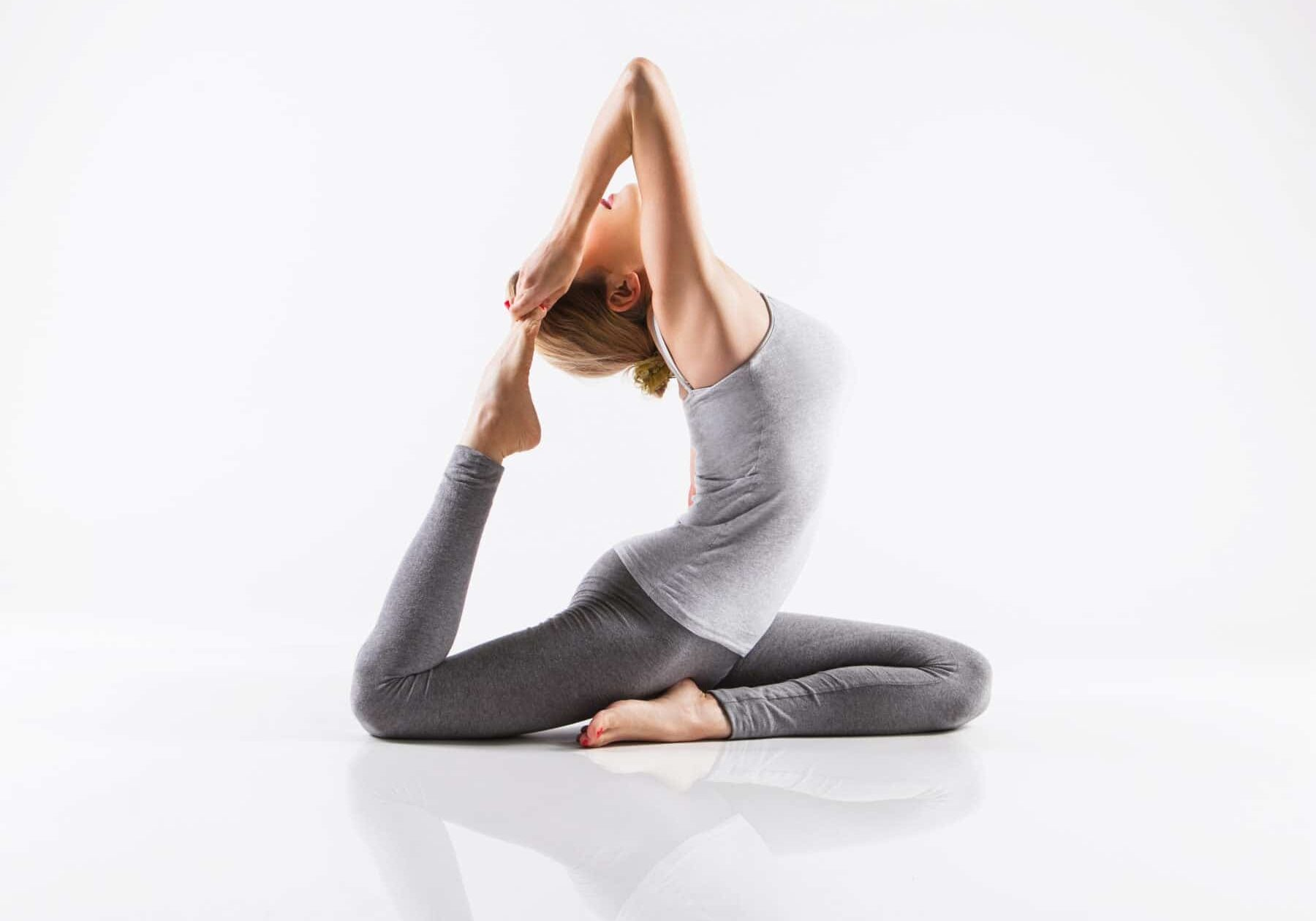 Yoga woman - pretty blonde in active wear doing yoga on white background. Woman doing fitness exercises